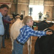 Evan Smith, Fairfield County, does a little touching up on his steer under the watchful eye of judge Dale Rains of Mercer, Pa., during 12-year-old Market Beef Showmanship.