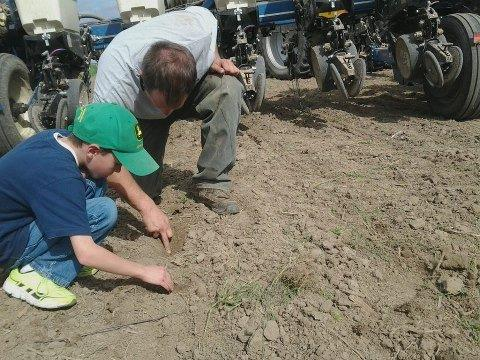 Alex Ward of Ward Farms of Urbana along with his oldest son, Max, take a quick break from the tractor cab to check how the planter is doing.