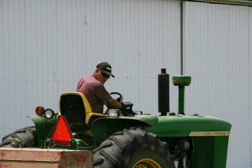 Harold Bush driving the tractor to bale hay.