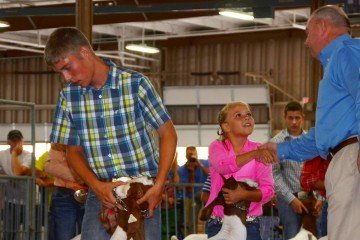 The judge shakes the hand of Michaela Ambos, 11, from Shelby County, to let her know that her goat is the Middle Weight Champion.