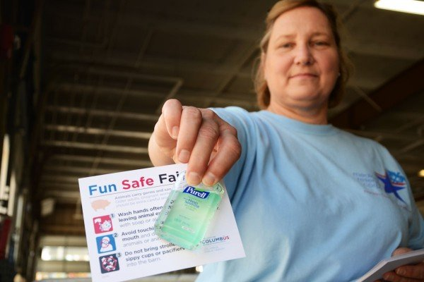 MaryAnn Janning, a Columbus Public Health Medical Reserve Corps volunteer, hands out free hand sanitizer to use when entering and leaving livestock barns.