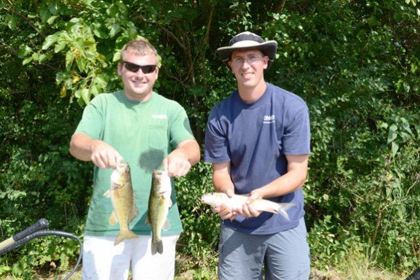 Ben Rich and Drew Phillips with the Ohio EPA hold fish they shocked to monitor stream quality.