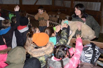 Kristin Reese holds a lamb for the fourth graders to pet.