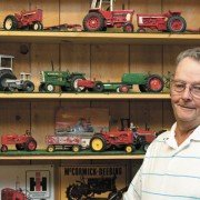 Gary Tabor stands beside one of many display units in his vast farm toy center.
