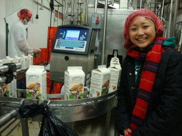 Zane Trace student Reina Fukushima stands next to the milk bottling line at Snowville Creamery