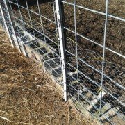 The ground was uneven under this section of fencing so I used cinder blocks to keep goats from going under it and broken off plastic posts were tied to it to so electric wire could be added to keep goats off of the fence.
