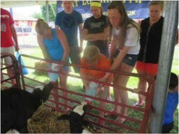 FFA Member Hunter Barga helps a boy bottle feed one of the calves.