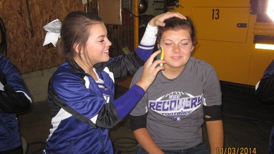 Pictured L to R - Fort Recovery Cheerleader Faith Hull applying a tattoo on the face of Makayla Post at the FFA Tailgate party prior to the homecoming football game.