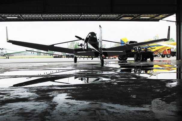 A Cessna crop duster waits its turn in the hanger.