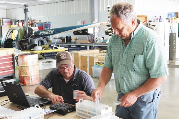 Luther Gibbs, right, weighs urea in a collection tube to test the accuracy of his application equipment.