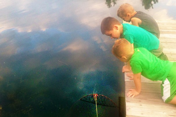 My son and his cousins check out a turtle trap off the dock.