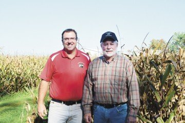 Doug Uher and Galen Koepke stand on Koepke's farm near the Portage River.
