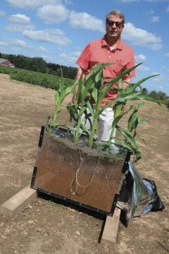 Zouheir Massri, with AgroLiquid, stands with a display that shows how the soil solution sampling method works.