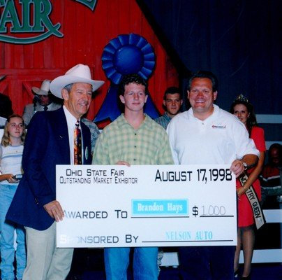 The Outstanding Market Exhibitor Program, funded by the Youth Reserve Program, recognizes the top overall exhibitors in the skillathon, showmanship and the market show. Governor George Voinovich helped recognize OME Brandon Hays at the 1998 Sale. Photo courtesy of the Ohio State Fair.