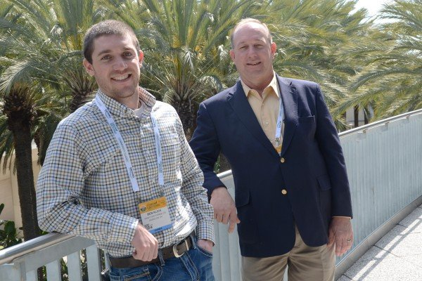 Ben Klick and Allen Armstrong solve some farm problems by the palm trees.